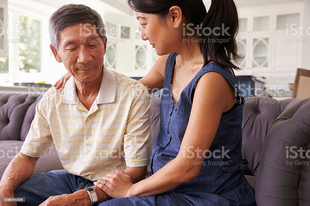 Adult Daughter Talking To Depressed Father At Home stock photo
