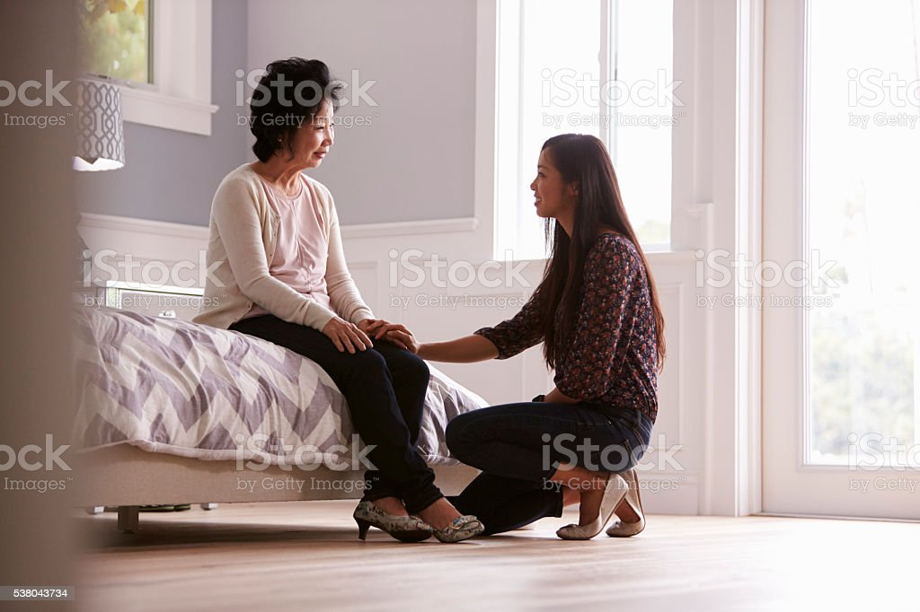 Adult Daughter Talking To Depressed Mother At Home stock photo
