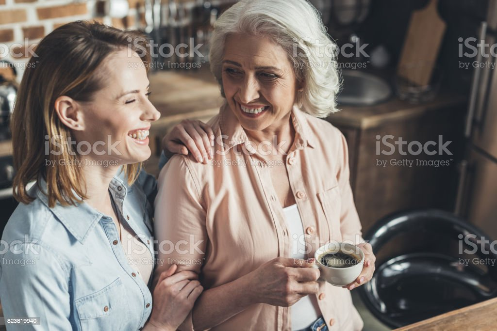 adult daughter talking with senior mother in kitchen stock photo