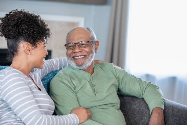 Adult daughter visits senior father in assisted living home stock photo