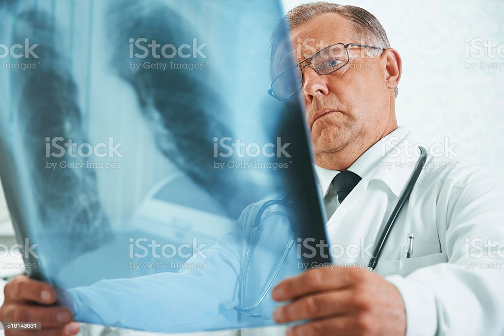 Adult doctor is analyzing x-ray image stock photo