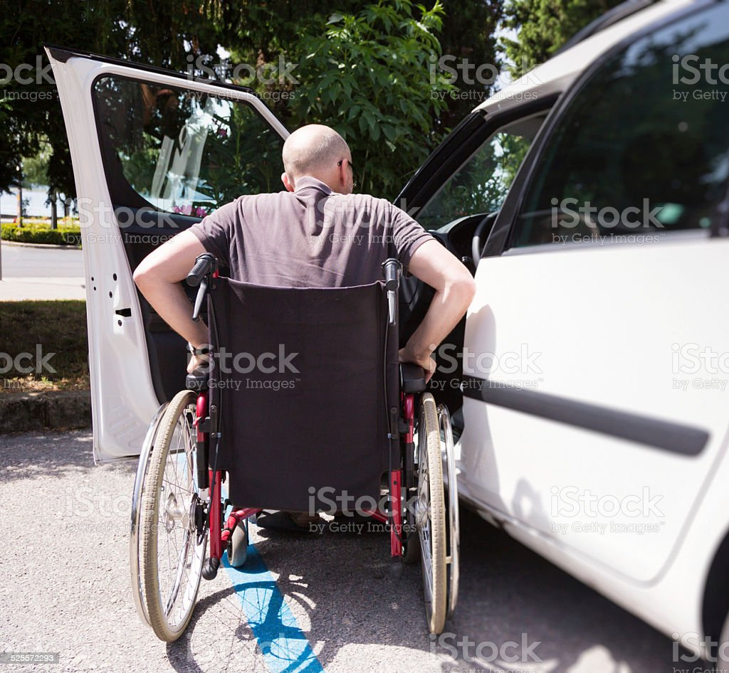 adult driver in wheelchair getting into the car stock photo
