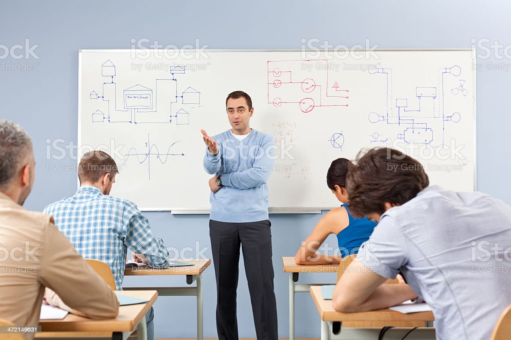Adult Ed Group of adult student attending a job training. Male teacher explaining diagrams technical systems drawn on whiteboard. 30-39 Years Stock Photo
