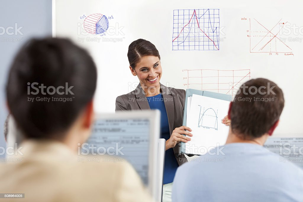 Adult Ed Group of adult student attending a job training. Female teacher standing in front of whiteboard and explaining diagrams. 30-39 Years Stock Photo