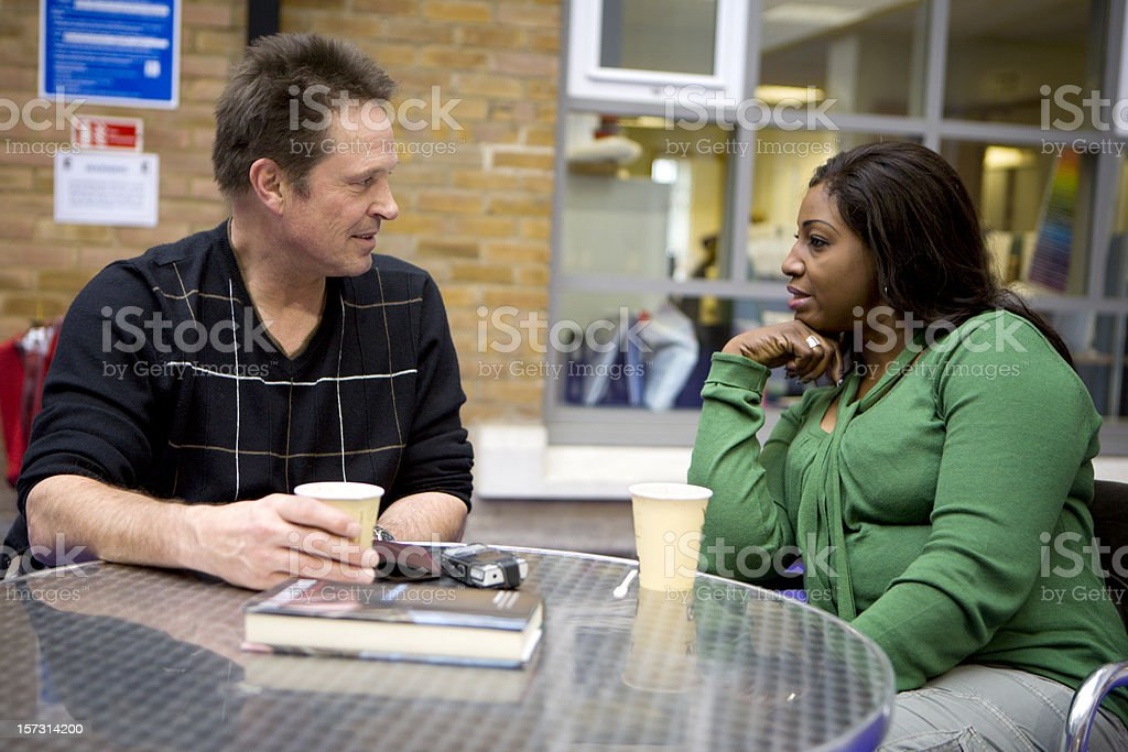 adult education: conversation between a mixed race couple over coffee royalty-free stock photo
