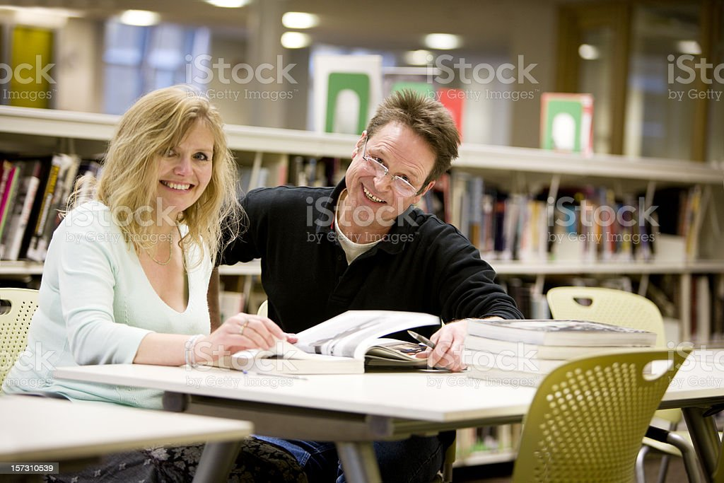 adult education: happy mature students working in their college library royalty-free stock photo