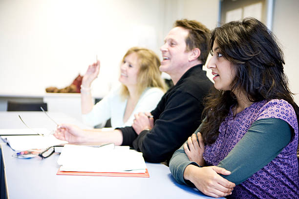 adult education: learning difficulties Anxious body language and a troubled look on the face of a mature student struggling to keep up with the lesson unlike her smiling classmates. illiteracy stock pictures, royalty-free photos & images