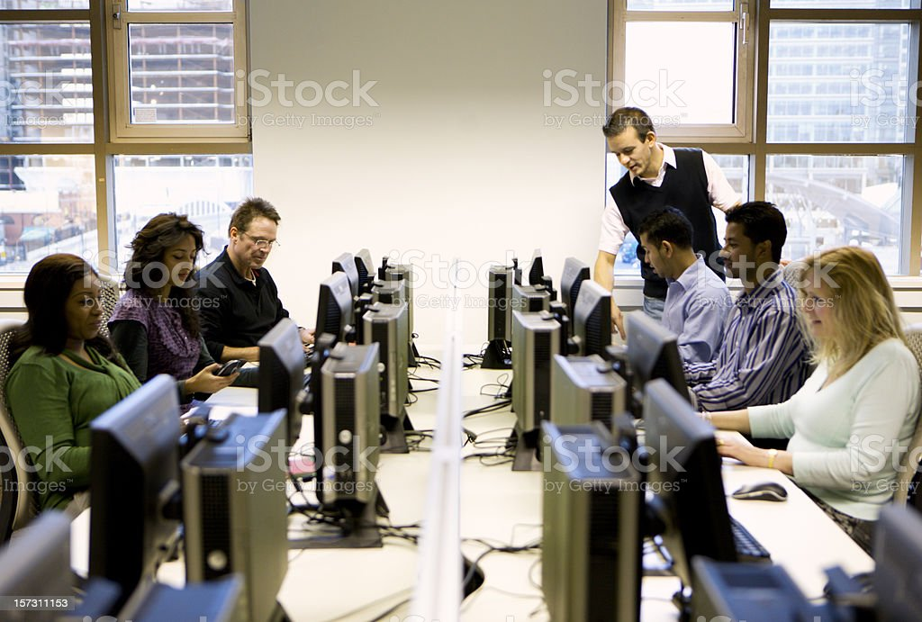 adult education: mature students working in a computer laboratory stock photo