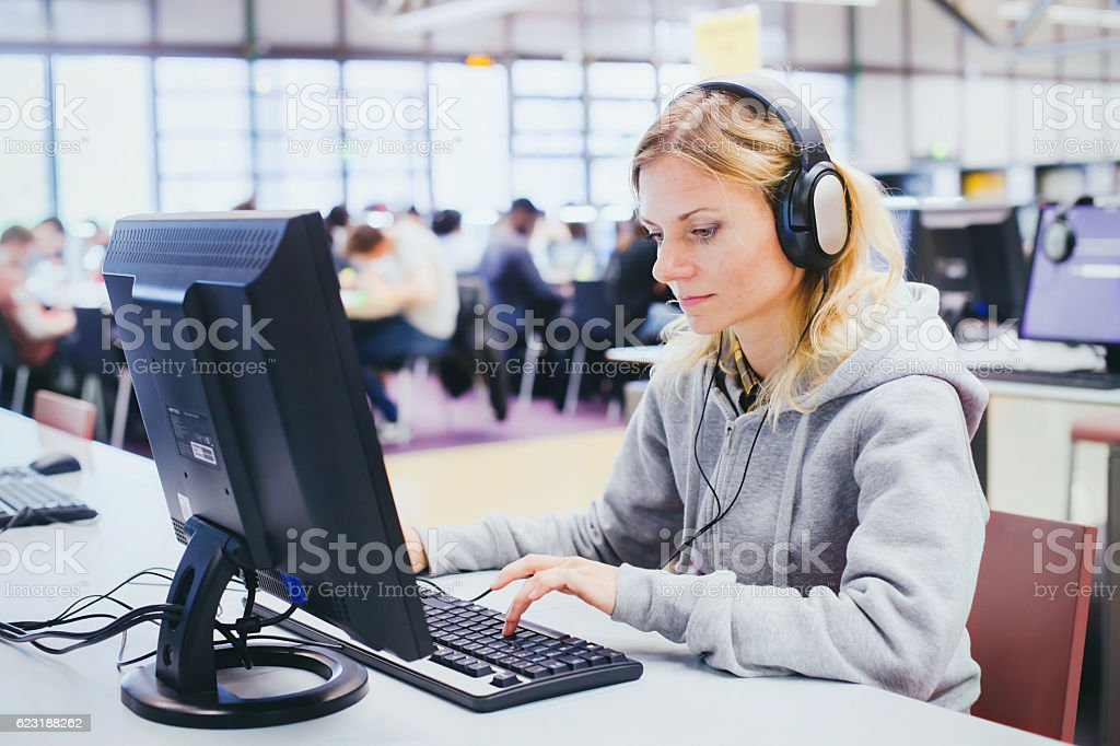 adult education, middle aged woman in library stock photo