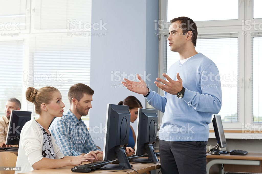 Adult education A teacher giving a lecture to a group of adult students attending computer course.  30-39 Years Stock Photo
