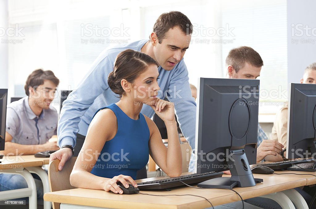 Adult education Group of adult students attending computer course. Focus on teacher talking with a young woman. 30-39 Years Stock Photo