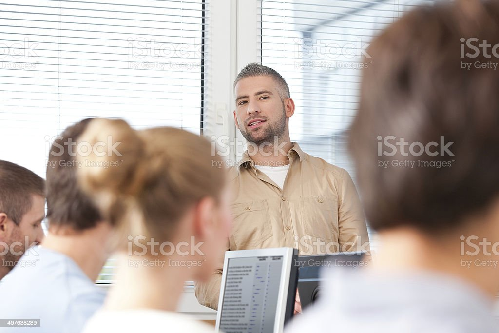 Adult education Group of adult students attending a job training. Focus on the male teacher standing in the background. 30-39 Years Stock Photo