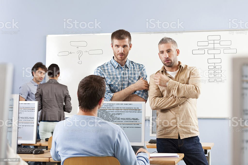 Adult education Group of adult students attending a job training. Focus on three discussing men. 30-39 Years Stock Photo