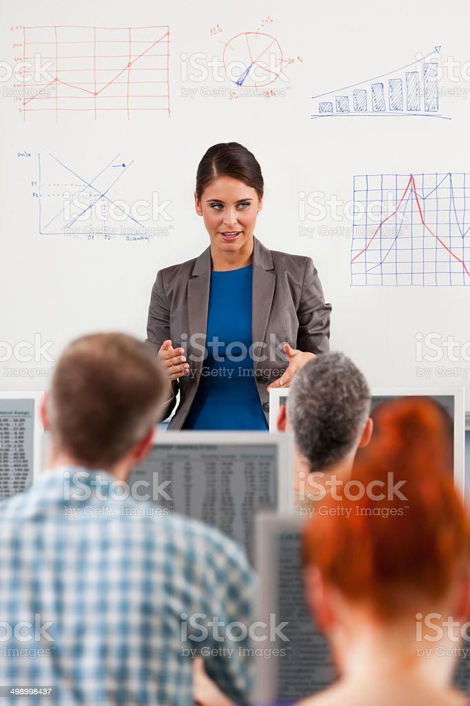 Adult education Group of adult students attending a job training. Focus on teacher explaining graphs drawn on a whiteboard. 30-39 Years Stock Photo
