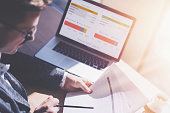 istock Adult elegant businessman in eyeglasses working at sunny office on laptop while sitting at wooden table.Coworker analyze document in his hands.Graphs and diagramm on notebook screen.Blurred background 815169044