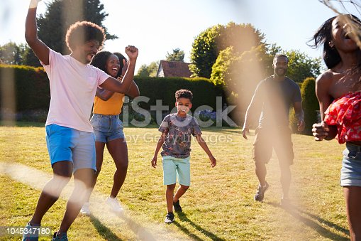 829627936istockphoto Adult family playing football with son celebrate goal 1045347180