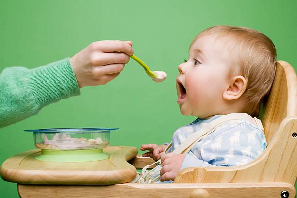Adulto alimentação de bebê - foto de acervo