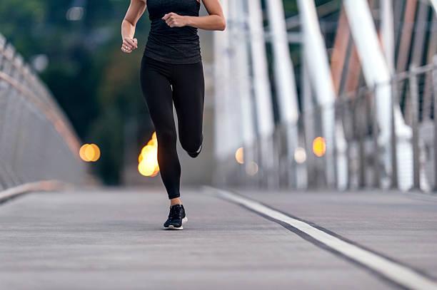 Adult female athlete figure running across a bridge stock photo