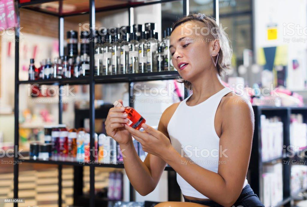 Adult female buyer choosing bottle of pheromones stock photo