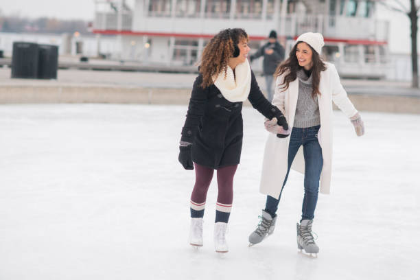 Adult Female Couple Ice Skating A gorgeous ethnic, female adult couple spend time together skating one afternoon. They are holding hands and smiling. ice skating stock pictures, royalty-free photos & images
