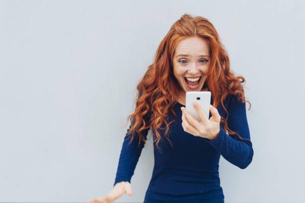 adult female exclaiming in awe at smart phone - buona notizia foto e immagini stock