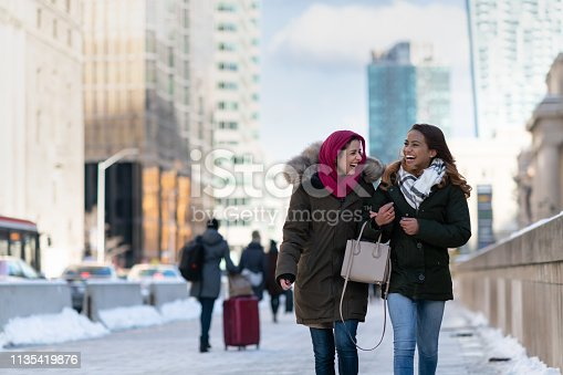 Two (2) attractive muslim adult female friends smile as they walk through the city. They are stylish and enjoying a cold winter stroll together.