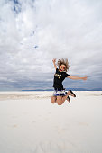 Adult female jumps in the sand dunes of White Sands National Monument. Concept for freedom, confidence, success