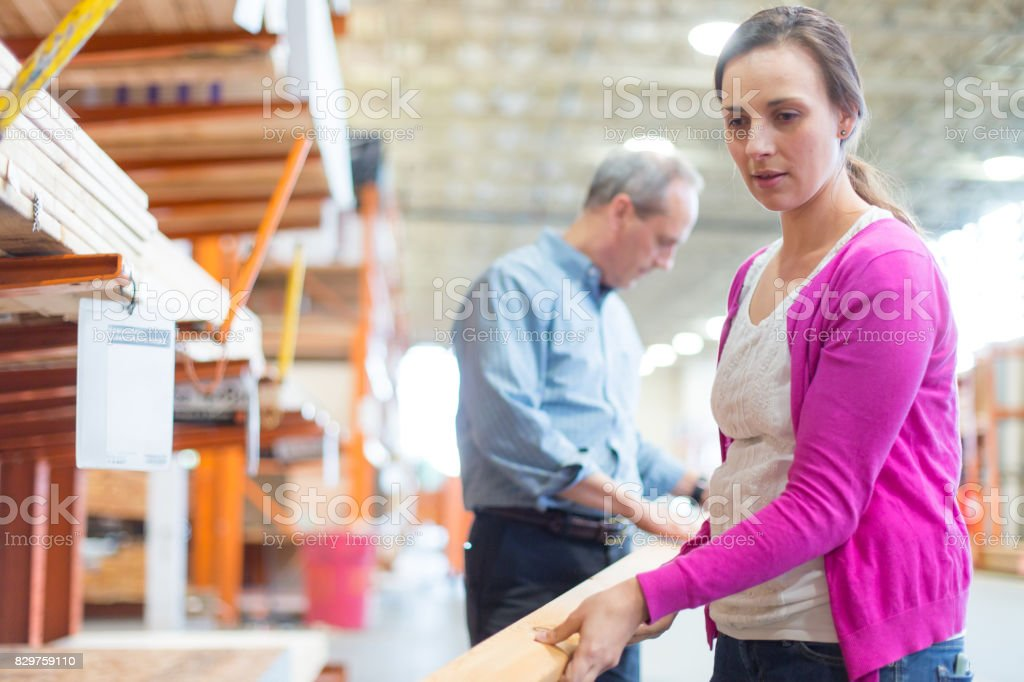 Adult female picking up 2x4 boards in hardware store stock photo