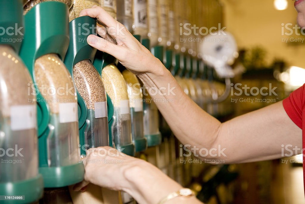 Adult Female Putting Grains into Bag at the Grocery Store royalty-free stock photo