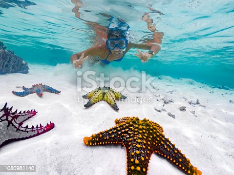 Adult Female Showing Peace Sign While Snorkeling Around Tropical Starfish.