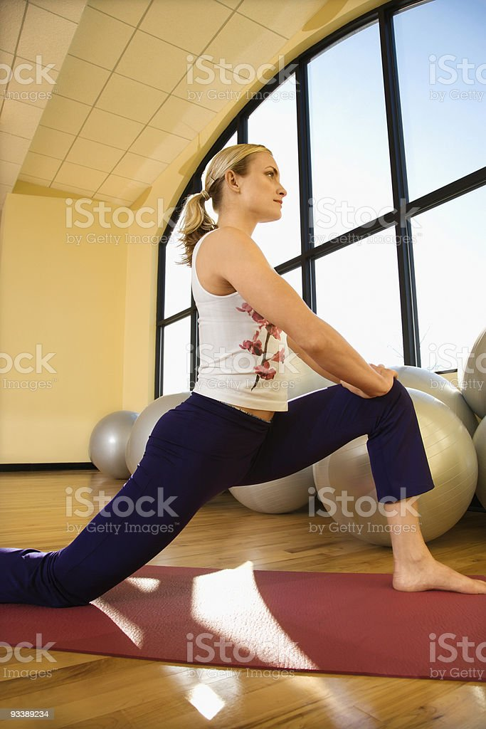 Adult female stretching at gym. royalty-free stock photo