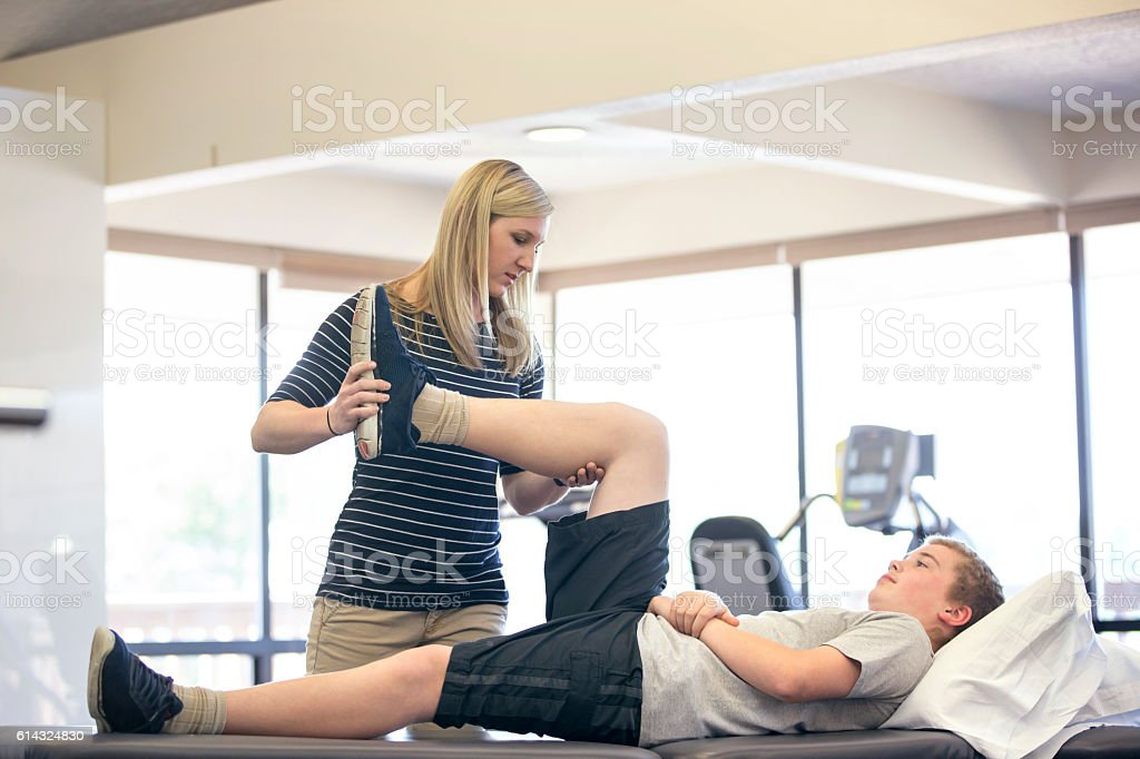 Adult female therapist stretching young males leg stock photo