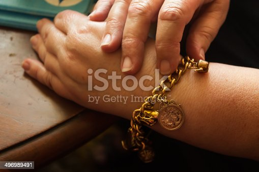 Adult female wearing an antique gold charm bracelet.