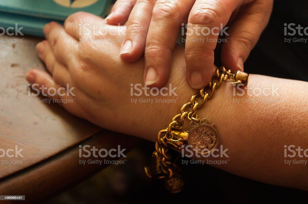 Adult female wearing a gold charm bracelet stock photo