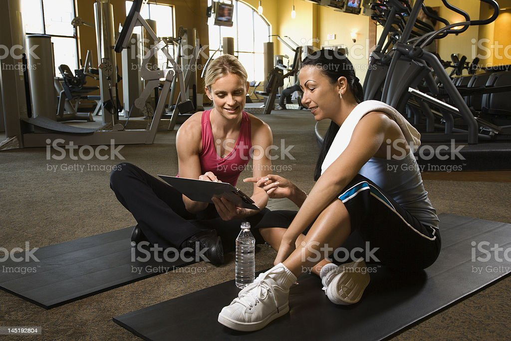 Adult female with personal trainer at gym. stock photo