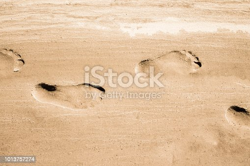 Adult footprints on wet white sandy coast on sunny day. No people. Water not visible. Closeup horizontal view from above.