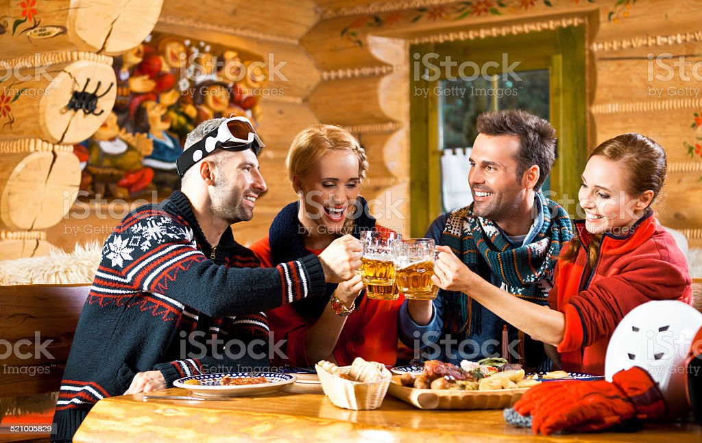 Adult friends having lunch, toasting with beer Two adult couples wearing winter clothes sitting in a mountain restaurant after skiing, enjoying dinner and toasting with beer. Adult Stock Photo
