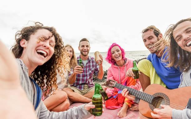 erwachsene freunde takinen selfie mit smartphone-kamera am beach-party im freien - glückliche menschen, die spaß beim musizieren und trinken bier - schwerpunkt zentrum jungs - technologie-trends und freundschaft konzept - tanz camp stock-fotos und bilder