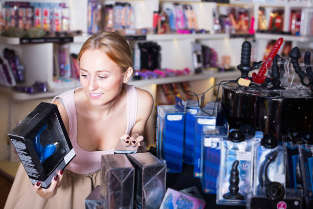 adult girl choosing toys in sex shop Portrait of joyful smiling young woman choosing toys for erotic games in sex shop sex toy stock pictures, royalty-free photos & images