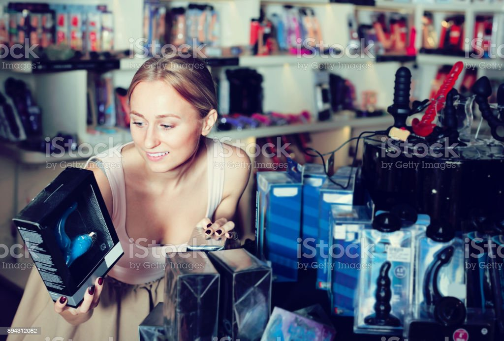 adult girl choosing toys in sex shop stock photo