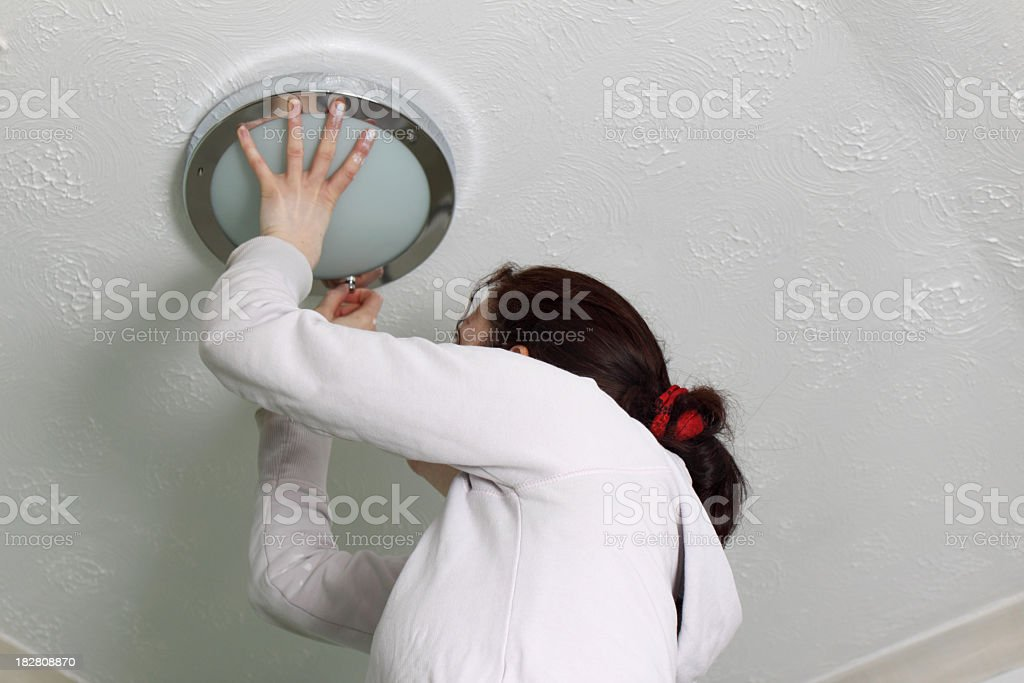 adult girl does DIY in bathroom replacing light fitting stock photo