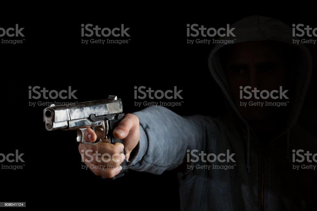Adult Gunman Aiming Handgun In Dark stock photo
