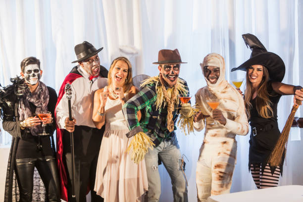 Adult halloween party A multi-ethnic group of six men and women at an adult halloween party with alcoholic beverages.  The costumes include an vampire, angel, witch, scarecrow, mummy and zombie. costume stock pictures, royalty-free photos & images
