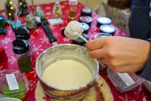erwachsenen hand hält er einen kuchen pop in geschmolzene weiße schokolade getaucht - lutscher cookies stock-fotos und bilder