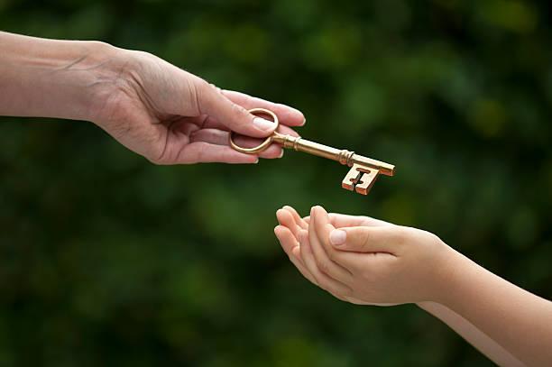 erwachsene hände schlüssel zum kind - übergeben stock-fotos und bilder