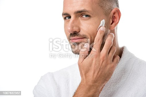 istock adult handsome man in bathrobe applying beauty cream on face isolated on white 1067832352