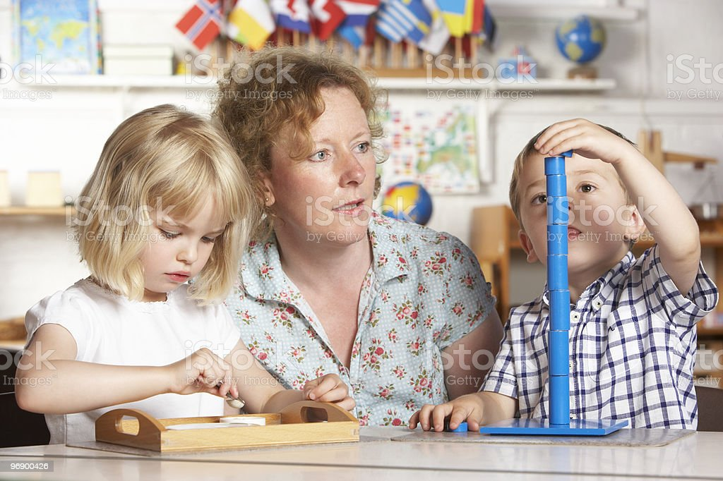 Adult Helping Two Young Children at Montessori/Pre-School royalty-free stock photo