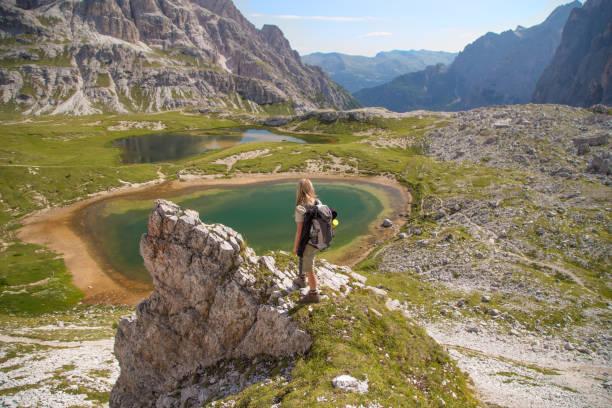 Adult hiker admiring beautiful alpine lakes in Dolomiti stock photo