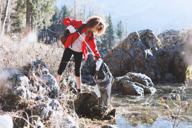 Adult Hiker Picking Up Garbage By a Lake stock photo