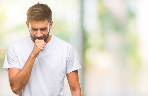 adult hispanic man over isolated background feeling unwell and coughing as symptom for cold or bronchitis. healthcare concept. - tossire foto e immagini stock